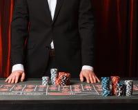 Homem que coloca uma aposta no casino fotos de stock