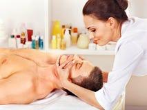 Homem que começ a massagem facial. fotos de stock