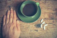 Homem que come comprimidos e café Imagem de Stock Royalty Free