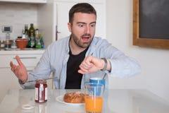 Homem que come o café da manhã mas para ir demasiado tarde trabalhar foto de stock