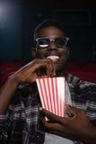 Homem que come a pipoca ao olhar o filme fotografia de stock royalty free