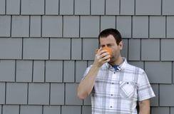 Homem que come uma bebida quente fora Imagem de Stock