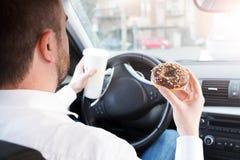 Homem que comem o café da manhã e condução assentada no carro foto de stock