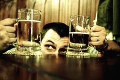 Homem que compara canecas de cerveja Foto de Stock Royalty Free