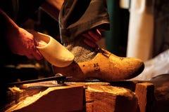 Homem que compara sapatas de madeira Fotos de Stock