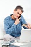 Homem que compra em linha com crédito Imagens de Stock Royalty Free