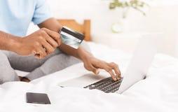 Homem que compra o produto em linha, usando o cartão de crédito para pagar foto de stock