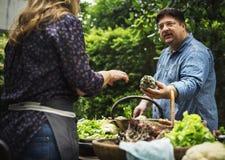 Homem que compra o vegetal orgânico fresco no mercado fotos de stock