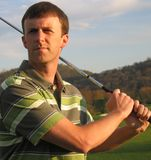 Homem que conduz a esfera de golfe no tempo do T foto de stock royalty free