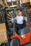 Homem que conduz o caminhão de empilhadeira no armazém Fotografia de Stock