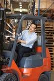 Homem que conduz o caminhão de empilhadeira no armazém Foto de Stock