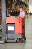 Homem que conduz o caminhão de empilhadeira no armazém Fotos de Stock