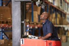 Homem que conduz o caminhão de empilhadeira no armazém Imagem de Stock Royalty Free