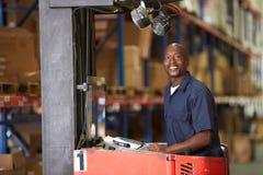 Homem que conduz o caminhão de empilhadeira no armazém Foto de Stock Royalty Free