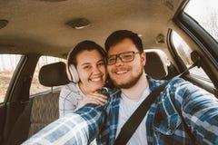 Homem que conduz o carro assento da mulher como o passageiro em assentos traseiros carro tr foto de stock