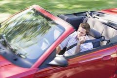 Homem que conduz o carro convertível usando o telemóvel Imagem de Stock Royalty Free