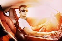 Homem que conduz o carro desportivo moderno Fotografia de Stock