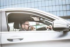 Homem que conduz o carro e que bebe o café fotografia de stock royalty free