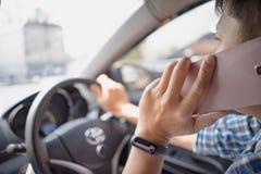 Homem que conduz o carro e que fala no telefone celular foto de stock