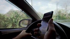 Homem que conduz o carro e que tenta encontrar o sentido com o navegador no telefone celular Mãos masculinas no volante Fim acima video estoque