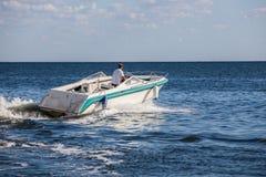 Homem que conduz um barco rápido imagem de stock