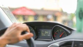 Homem que conduz um carro através da vila Foto de Stock
