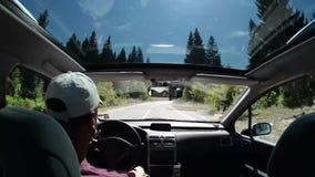 Homem que conduz um carro na estrada secundária vídeos de arquivo