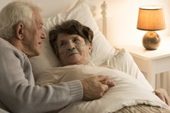 Homem que consola a esposa doente imagem de stock royalty free