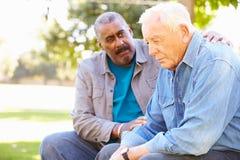 Homem que consola o amigo superior infeliz fora foto de stock