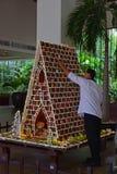 Homem que constrói a grande casa de pão-de-espécie em uma instalação comercial foto de stock royalty free