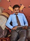 Homem que consulta no PC da tabuleta Fotografia de Stock