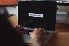 Homem que consulta no portátil, pronto para registrar-se, botão na tela fotografia de stock royalty free