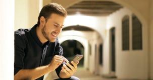 Homem que consulta o índice esperto em linha do telefone na noite vídeos de arquivo