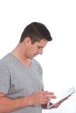 Homem que consulta o Internet em uma tabuleta Fotos de Stock Royalty Free