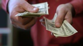 Homem que conta notas de dólar O fim acima das mãos masculinas conta o dinheiro do dinheiro vídeos de arquivo