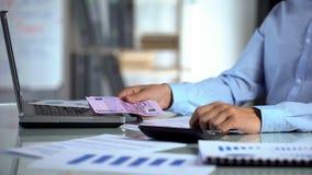 Homem que conta o euro, a renda da empresa e a despesa, lucro de negócio, orçamento imagens de stock
