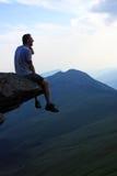 Homem que contempla sobre uma rocha Imagens de Stock