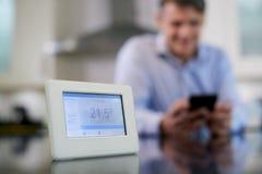 Homem que controla o medidor esperto do aquecimento central usando o App no móbil fotografia de stock
