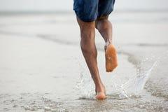 Homem que corre com os pés descalços na água Imagem de Stock