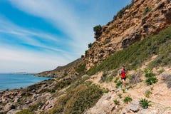 Homem que corre em montanhas e no beira-mar inspirados Imagens de Stock Royalty Free