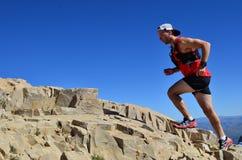 Homem que corre em uma fuga de montanha alta fotografia de stock