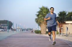 Homem que corre em uma pista de atletismo perto da praia Fotos de Stock