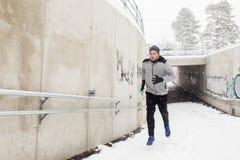 Homem que corre fora do túnel do metro no inverno Fotografia de Stock Royalty Free