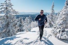 Homem que corre na neve Fotografia de Stock Royalty Free