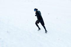 Homem que corre na neve fotos de stock