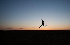Homem que corre no céu do por do sol no monte Imagens de Stock