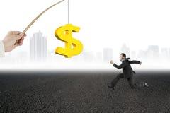 Homem que corre o citysca dourado da estrada asfaltada da atração da pesca do sinal de dólar Fotos de Stock Royalty Free