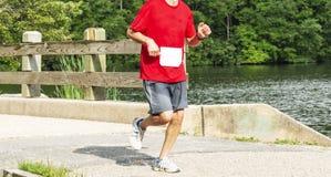 Homem que corre sobre a ponte pelo lago imagem de stock