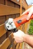 Homem que corta a cerca de madeira fotografia de stock