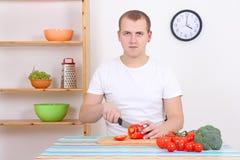 Homem que corta a pimenta vermelha na cozinha Imagens de Stock